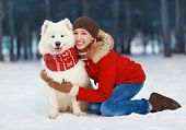 stock photo of joy  - Joyful beautiful stylishly dressed young woman in red jacket hugging white Samoyed dog outdoors in the park on a winter day - JPG