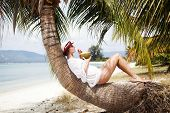 Woman drinkind coconut on exotic beach