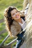 Beautiful young woman relaxing under a hay stack in autumn