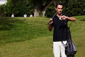 Golfer holding driver while checking time on his wear watch