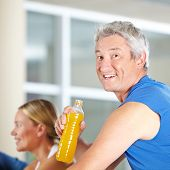 Elderly man drinking isotonic sports drink in a gym