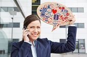 Smiling business woman with smartphone holding speech bubble with digital icons