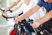 Hands of senior people in gym on bikes