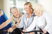 Fitness trainer measuring time for senior people on bikes in gym