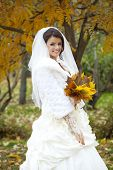 Portrait of a beautiful smiling bride in autumn park