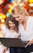 family, childhood, holidays, technology and people concept - smiling mother and little girl with laptop computer over red lights background
