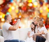 family, holidays, technology and people - smiling mother, father and little girls with camera over r