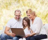 family, childhood, holidays, technology and people concept - smiling family with laptop computer over golden lights background
