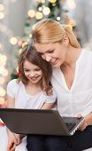 family, childhood, holidays, technology and people - smiling mother and little girl with laptop comp