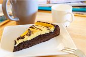 Browny Cheese Cake On White Dish With Coffee Cup And Relaxing Magazine Table Top Scene