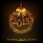 Happy New Year 2015 celebrations concept with golden Christmas ball on brown background.