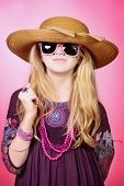 Little fashion girl in beautiful dress, beads and sunglasses posing over pink background.