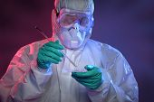 Scientist in Hazmat suit and protective gear working with virus on Petri dish