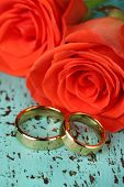 Wedding rings on wedding bouquet, close-up, on color wooden background