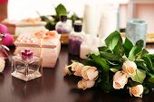 Beautiful roses, perfumes on table near mirror
