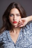 Fashion portrait of beautiful woman with red lips in knitted sweater
