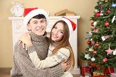 Nice love couple near Christmas tree. Woman and man celebrating Christmas