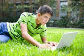 Young male college student use laptop at campus