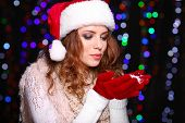 Portrait of woman in scarf and gloves on bright lights background