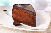 Piece of chocolate cake on saucer on light background