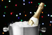 Bottle of champagne in bucket with ice, on black background with color lights