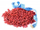 Goji berries and blue measuring tape line isolated on white