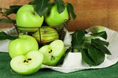 Ripe apples in metal basket with napkin on wooden background
