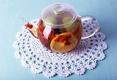 Fruit drink in teapot on lace napkin on light blue wooden background