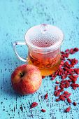 Goji berries drink in glass cup and ripe apple on old blue wooden background