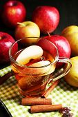 Apple cider with cinnamon sticks and fresh apples on wooden background