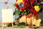 Beautiful autumn composition with paper blank on wooden background