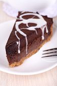 Piece of chocolate cake on plate on wooden table on teapot background