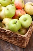 Ripe apples in basket on wooden table close-up