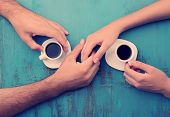 Coffee cups and holding hands at the wooden table