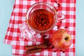 Goji berries drink in glass cup, ripe apple and cinnamon on red checkered napkin on light blue woode