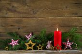 Classical christmas decoration: red candle and brunches on wooden old background.