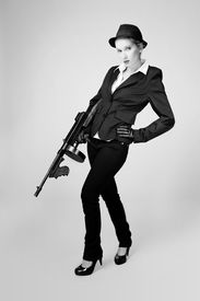 """stock photo of tommy-gun  - Mafia style fashion studio portrait - nice young woman posing with """"Tommy"""" gun for figure and portrait photos in retro criminal style. ** Note: Soft Focus at 100%, best at smaller sizes - JPG"""