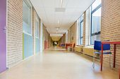 stock photo of school building  - Long straight corridor with furniture in school building - JPG