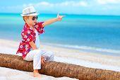 image of gangster  - cute boy playing a gangster on summer beach - JPG