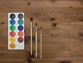 palette with paint and brushes on the wooden background