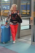 Woman at a railway station with big luggage