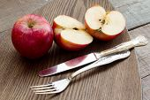 Red Apples Over Wooden Plate With Silveware