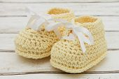 image of booty  - Retro Baby Booties Pale Yellow Baby Booties on a grunge wood background - JPG