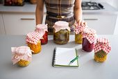 picture of pickled vegetables  - Closeup on notepad and young housewife with jars of pickled vegetables - JPG