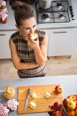 Young Housewife Eating Apple In Kitchen
