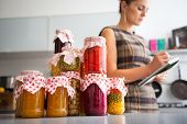 pic of pickled vegetables  - Closeup on jars with homemade fruits jam and pickled vegetables and housewife writing in notepad in background - JPG