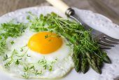 Breakfast of fried eggs, asparagus and watercress salad