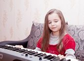 Little Girl Playing On A Synthesizer