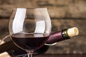 stock photo of merlot  - Red wine in wineglass against corked bottle on wood background - JPG