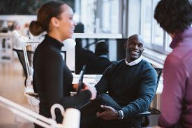 picture of coworkers  - Happy african man sitting at desk with coworkers smiling - JPG
